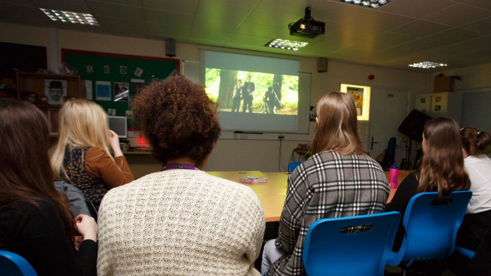 5 people in film club watching screen