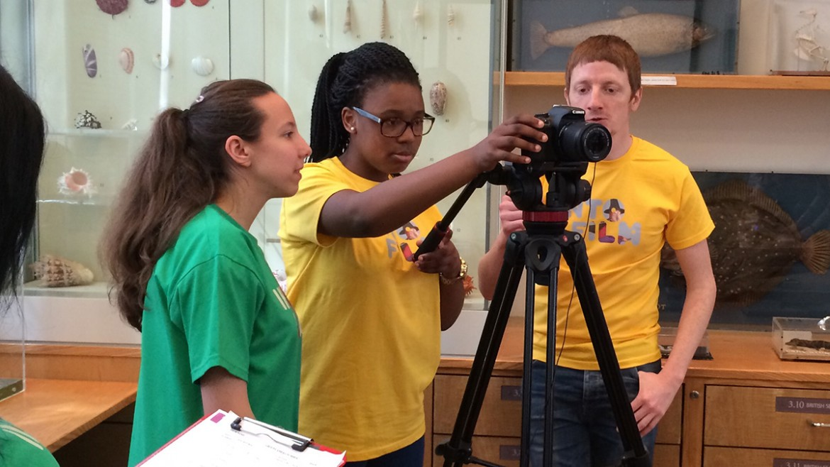 Two girls behind camera with one boy to side, in Into Film t-shirts.