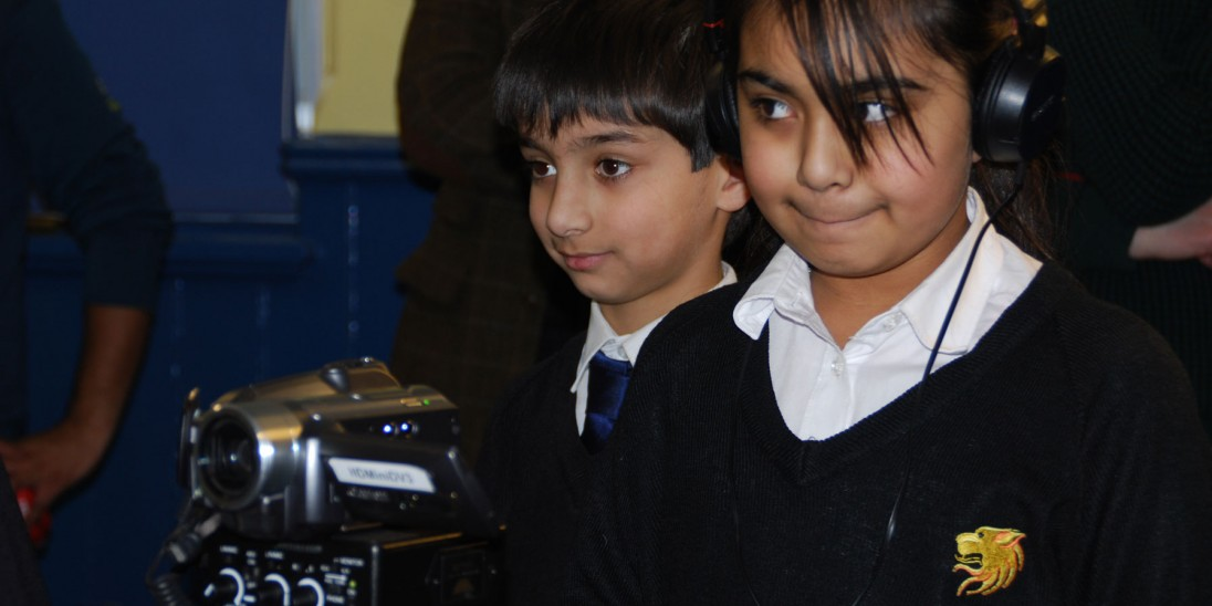 A picture of children using filmmaking equipment