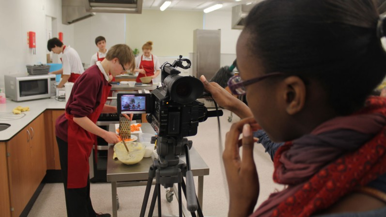 Secondary students using filmmaking equipment